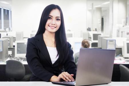 secretaria: Empresaria est� sonriendo mientras trabajaba en su oficina Foto de archivo