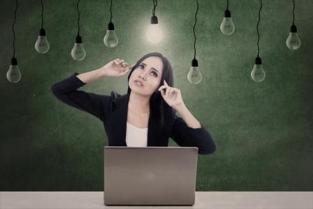 light bulbs: Hermosa mujer de negocios est� pensando en ideas bajo las bombillas, mientras trabaja con su computadora port�til