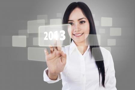 Beautiful businesswoman is touching 2013 icon using modern technology Stock Photo - 17249698