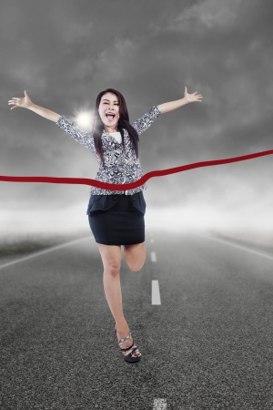 Young businesswoman winning the race with storm clouds background photo