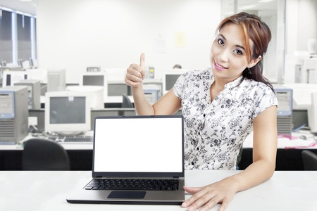 Young businesswoman hold thumb up while showing blank laptop monitor in office photo