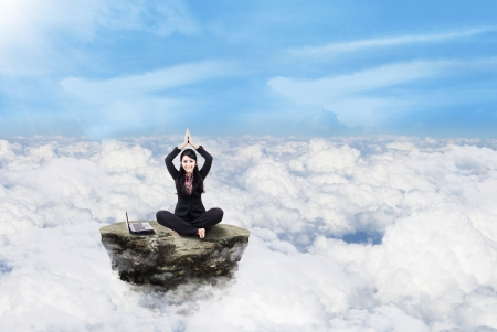 Beautiful businesswoman is meditating above clouds Stock Photo - 17249694