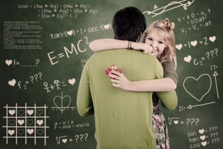 gets: A girl is smiling because he gets a present from her boyfriend in classroom