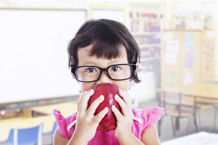 Portrait of asian female preschooler eating red apple at class photo