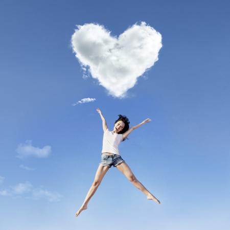 Beautiful girl is jumping under a heart shape cloud photo