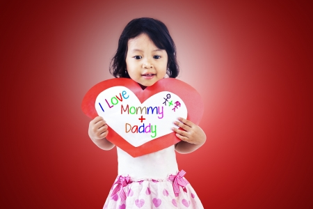 Girl is holding love card for her parents on red background photo
