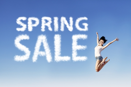 short sale: Young girl is jumping beside spring sale shape clouds under blue sky Stock Photo