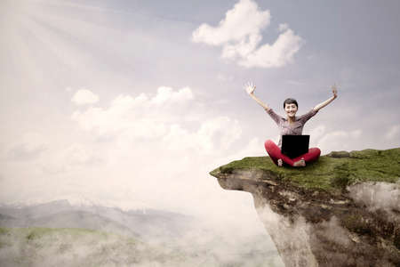 horizontal: A young girl is sitting on a high mountain with her laptop and arms raised