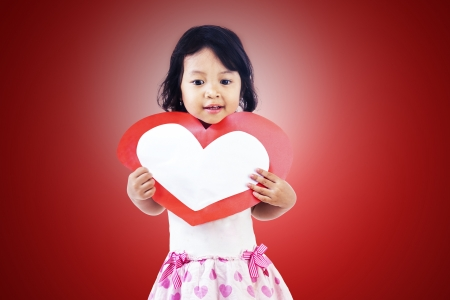 Cute girl with blank love card on red background photo