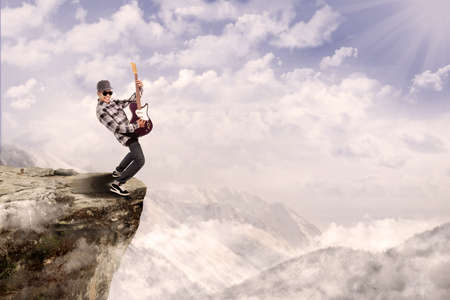 cliff: Young male guitarist is playing outdoor on top of a mountain