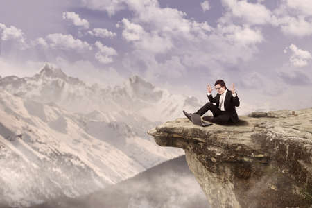 cliff edge: Businessman is sitting happily while working on his laptop on top of a mountain