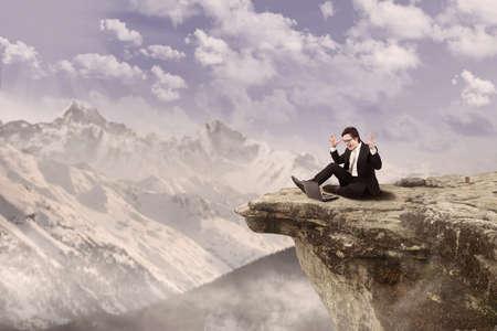 bordi: Uomo d'affari � seduto tranquillamente mentre si lavora sul suo computer portatile sulla cima di una montagna