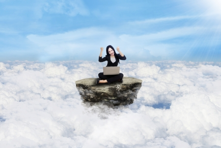 Happy beautiful businesswoman sitting on the rock above clouds Stock Photo - 17249654