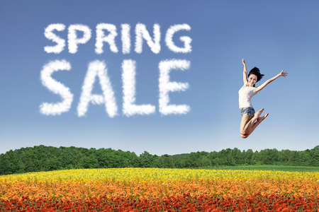 Beautiful woman is jumping over colorful flowers during spring sale photo