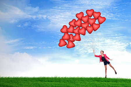 balloon woman: Young woman holding many red heart shape baloons on a green field