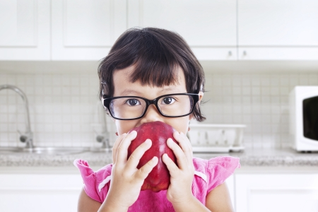 Portrait of nerd toddler is eating red apple in the kitchen photo
