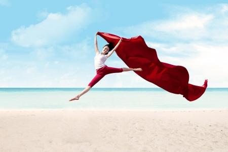 美しい女性の赤い大きなスカーフと海でジャンプ