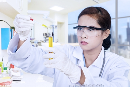 chinese medicine: Young female scientist holding yellow liquid in a flask