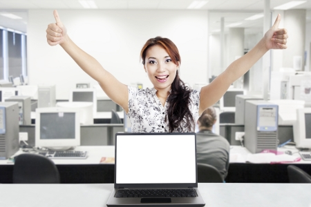 Young businesswoman hold thumbs up behind a blank monitor in the office photo