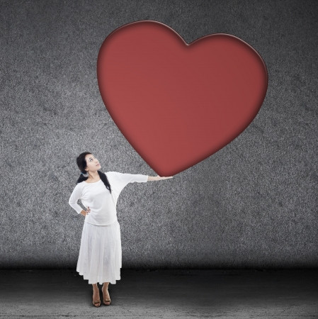 big woman: Beautiful woman in white holding big blank red heart sign on grey background Stock Photo
