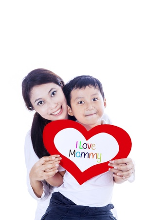 A cute boy is giving love card to his mother on white background photo