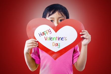 Asian boy is holding valentine card on red background photo