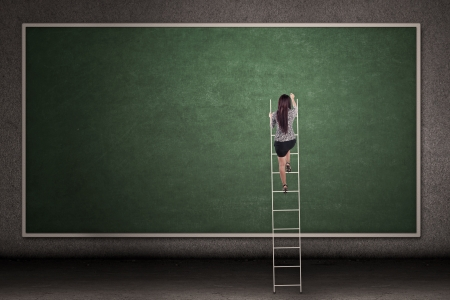 woman stairs: Businesswoman is climbing a ladder in front of a blackboard
