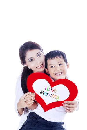 Cheerful boy is giving a love card to his mother on white background photo