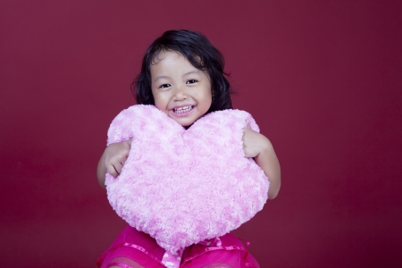 Cute girl is smiling while holding pink heart pillow on pink background photo