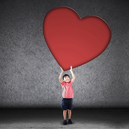 hispanic boy: Cute Asian boy is holding huge love cutout on grey background Stock Photo