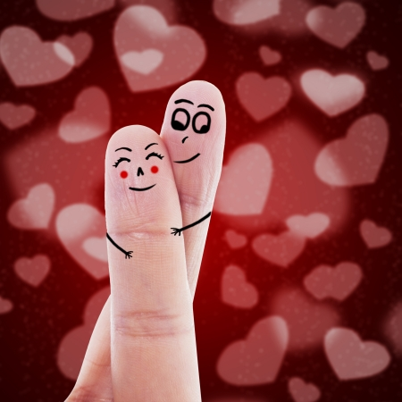 Cute finger sign language of a guy hugging his girlfriend on red background photo