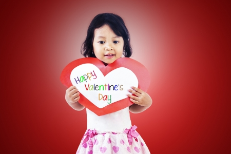 Cute girl is holding valentine card on red background photo