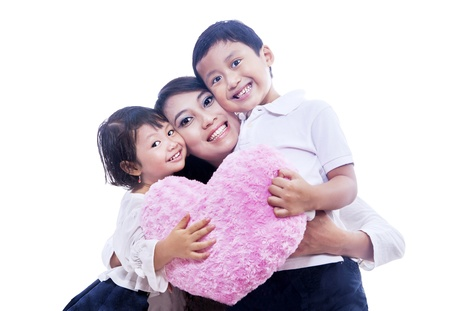 Two happy children is giving their mom a hug while holding pink pillow on isolated white background photo