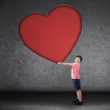 paper heart: A happy boy is holding huge love symbol on grey background