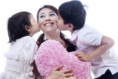 indonesisch: Gelukkige moeder gekust door haar dochter en zoon op een witte achtergrond Stockfoto