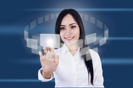 Businesswoman is pressing virtual icons on blue background photo