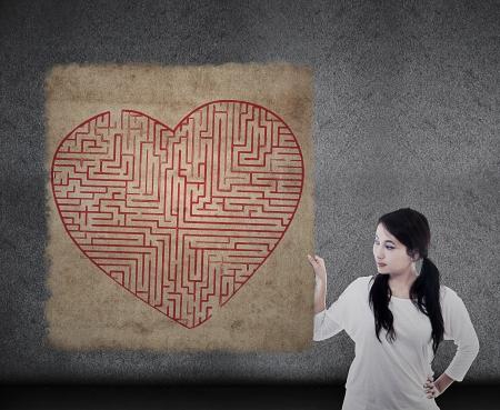 Beautiful woman is holding heart shape maze map photo
