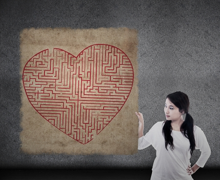 challange: Beautiful woman is holding heart shape maze map Stock Photo