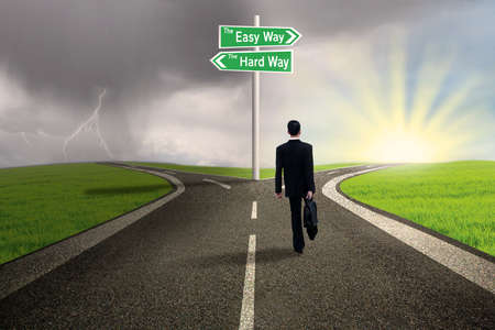 Businessman is choosing the easy way lane over the hard way lane with stormy background photo
