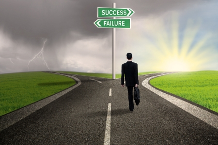 사업가는 성공 또는 실패의 기호 도로에 걷고있다 스톡 콘텐츠