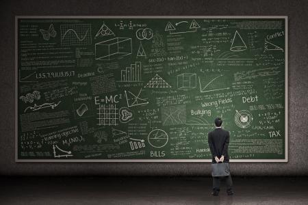 profesor: Hombre de negocios est� mirando una pizarra enorme mano dibujada en un sal�n de clases Foto de archivo