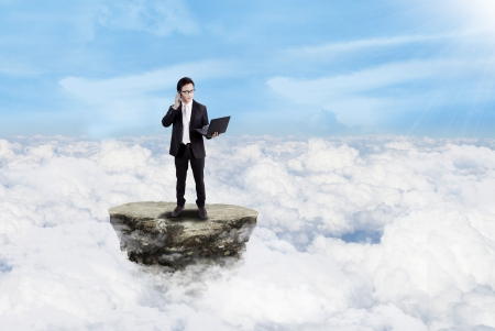 Businessman is calling while holding his laptop above the clouds Stock Photo - 17533493