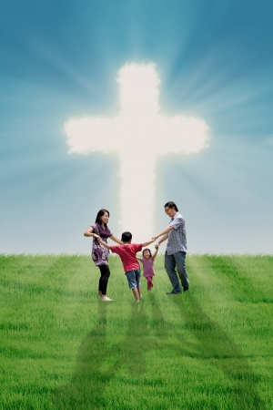 cristianismo: La familia feliz est� bailando en la Cruz brillante Foto de archivo
