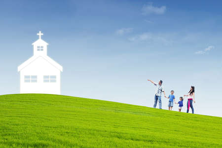 people in church: Christian family is walking to the church on top of a hill Stock Photo