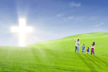 familia cristiana: Los familiares están caminando alegremente hacia la cruz luminosa en el parque Foto de archivo