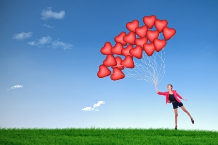 A girl is holding many red balloons with heart shape on green field photo