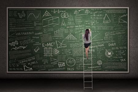 profesor: Empresaria est� subiendo una escalera mirando a la pizarra dibujado a mano en un sal�n de clases