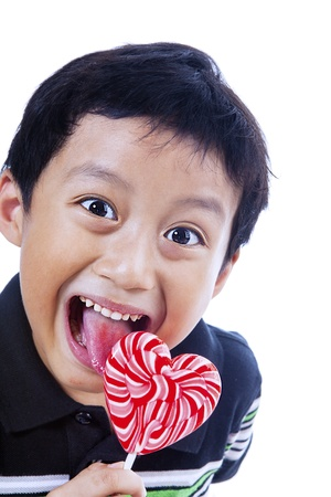 smile close up: A happy Asian boy is holding a heart shape lollipop on white background