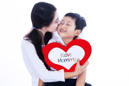 mom kiss son: A boy is giving a love card to his mom on mother