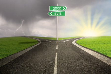 Road sign of good vs evil on stormy background Stock Photo
